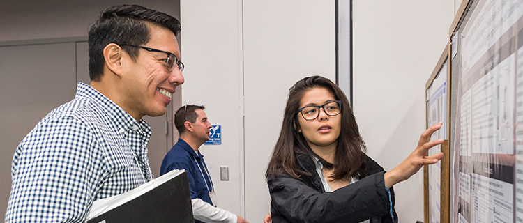 Scholars engage with faculty judges and fellow scholars as they present their research at the 2018 UC LEADS Symposium at UCSB